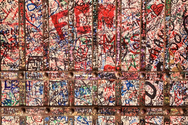 Escritos en una pared y un fondo de puerta de hierro