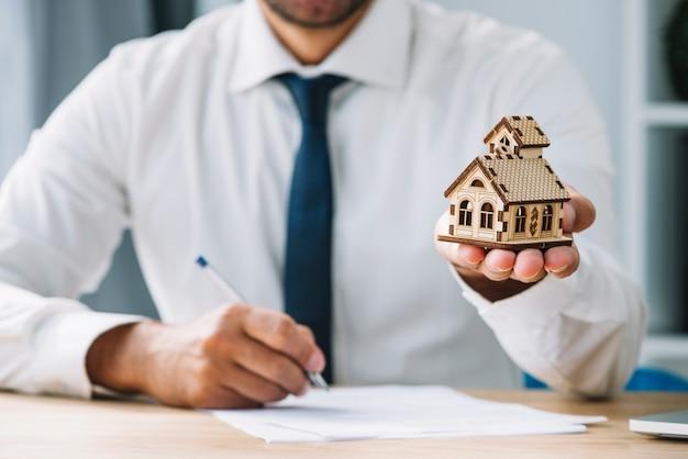 Escritura del agente inmobiliario que sostiene la casa