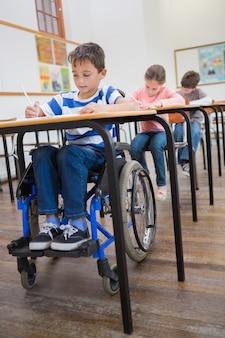 Escritura del alumno discapacitado en el escritorio en el aula