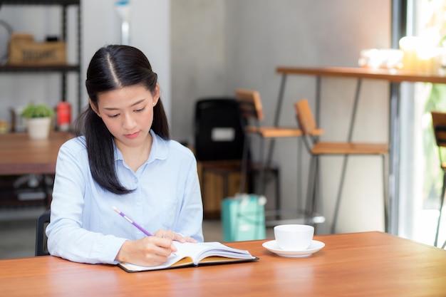 Escritura asiática de la mujer del negocio hermoso en el cuaderno en la tabla.