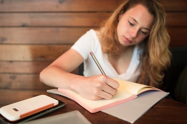 Escritura atractiva de la mujer joven en cuaderno