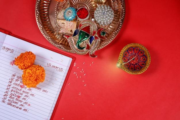 La escritura de la caligrafía en hindi shubha labh significa bondad y riqueza, sobre un cuaderno de contabilidad rojo, diya,