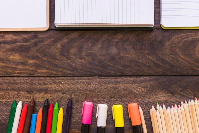 Escritura de útiles cerca de cuadernos