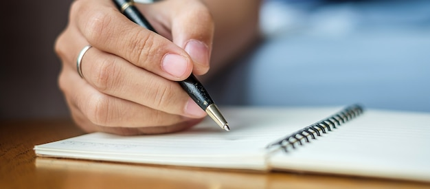 Escritura de la empresaria algo en el cuaderno en oficina