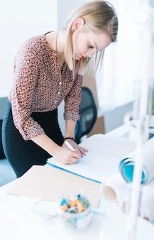 Escritura de la empresaria en el papel sobre el escritorio de oficina