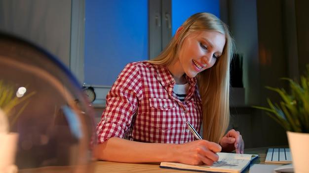 Escritura femenina alegre en planificador diario mujer rubia joven vivaz en camisa a cuadros casual sentado en el escritorio de madera con cuaderno sosteniendo bolígrafo de metal y mirando a cámara sonriendo por la noche en una habitación oscura