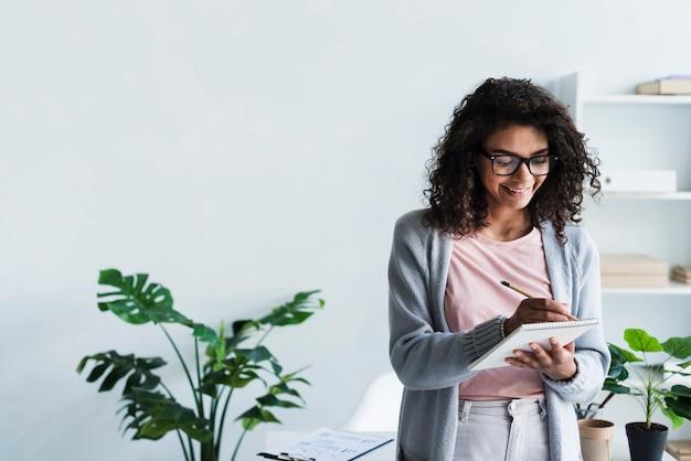 Escritura femenina joven sonriente en scratchpad en lugar de trabajo