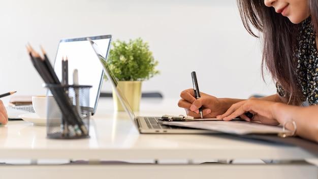 Escritura femenina de negocios, tomando notas en el cuaderno, espacio de trabajo de oficina