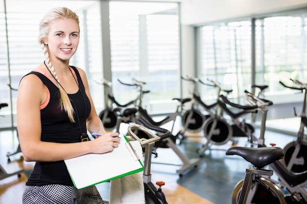 Escritura femenina sonriente del instructor en el tablero en el gimnasio
