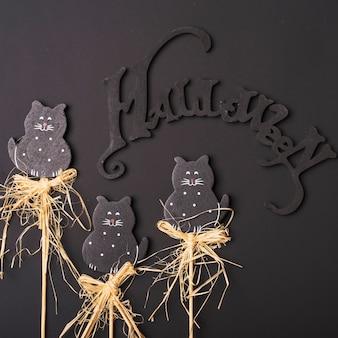 Escritura de halloween cerca de los gatos