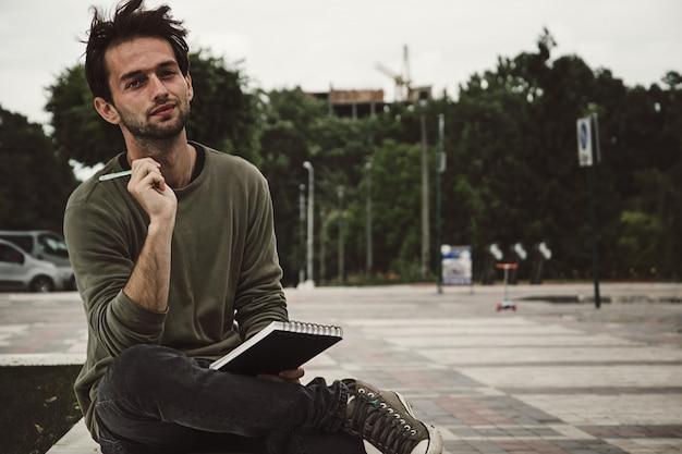 Escritura del inconformista del hombre joven en cuaderno en la calle, vista lateral.