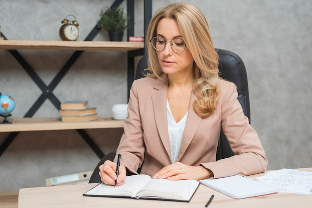 Escritura joven rubia de la empresaria en el diario con la pluma en la oficina