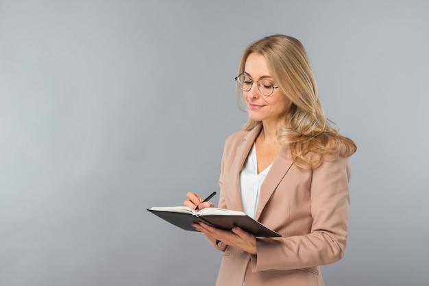 Escritura joven sonriente de la empresaria en el diario con la pluma contra fondo gris