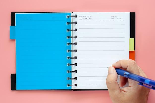 Escritura de la mano en un cuaderno en blanco abierto con la pluma en fondo rosado