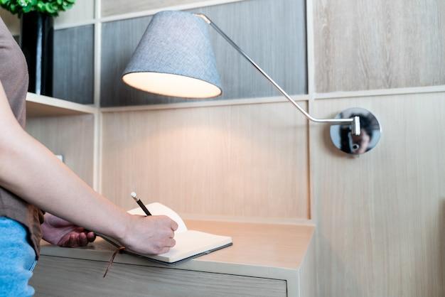 Escritura de la mano en el cuaderno en el escritorio con lámpara