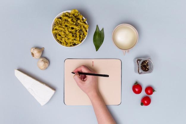 Escritura de la mano humana en el diario que rodea por ingrediente de pasta