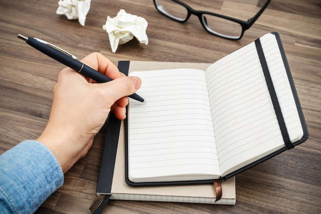 Escritura de la mano de la mujer en el cuaderno