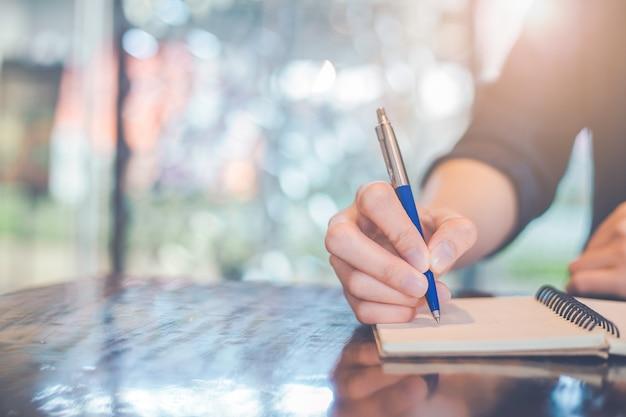 Escritura de la mano de la mujer en una libreta con una pluma en la oficina.