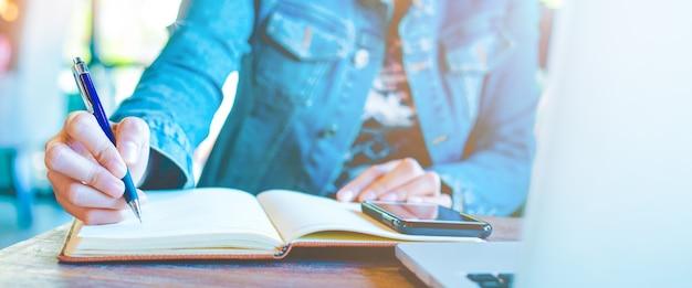 Escritura de la mano de la mujer en la libreta con una pluma