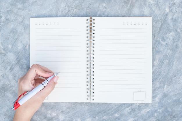Escritura de la mano de la mujer del primer en el cuaderno