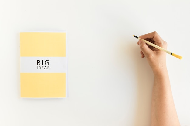Escritura de la mano de una persona en el fondo con diario de grandes ideas