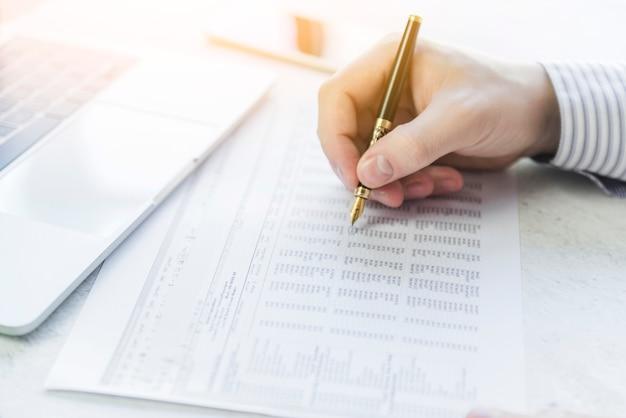 Escritura de la mano con la pluma en la mesa en el papel