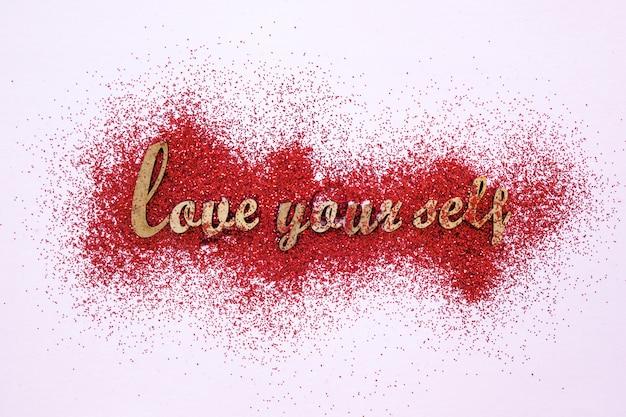 Escritura motivacional sobre purpurina roja.