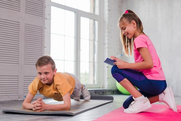 Escritura de la muchacha en el tablero mientras que mira al ejercicio del muchacho