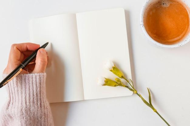 Escritura de la mujer en el cuaderno en blanco con la pluma sobre el fondo blanco
