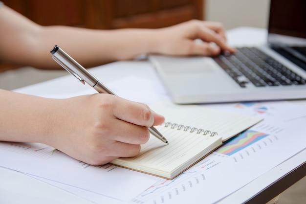 La escritura de la mujer hace la nota y usando la oficina de las finanzas del ordenador portátil en casa.