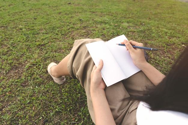Escritura de la mujer joven en el cuaderno con el lápiz en hierba en parque al aire libre.