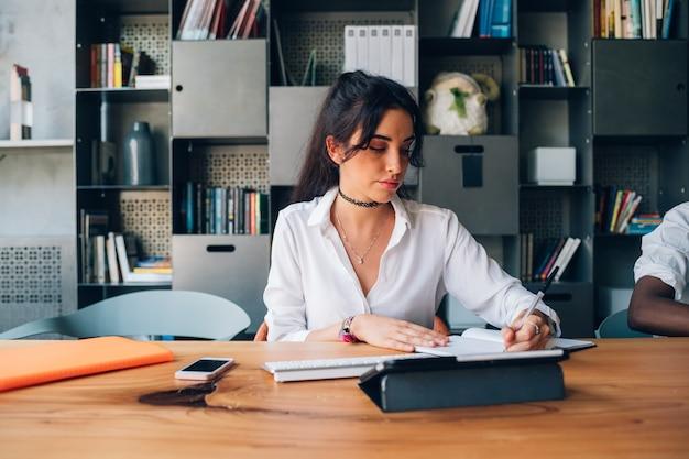 Escritura de la mujer joven durante la reunión en oficina moderna