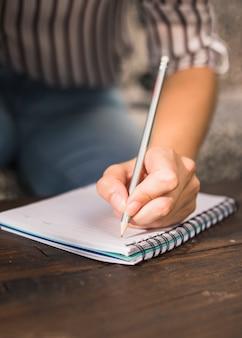 Escritura de la mujer con el lápiz en el cuaderno espiral sobre la tabla de madera