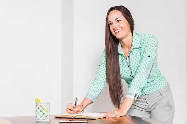 Escritura de la mujer de negocios en su cuaderno