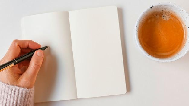 Escritura de la mujer con la pluma en el cuaderno en blanco con café sobre el fondo blanco