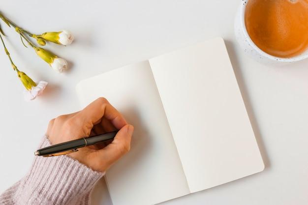 Escritura de la mujer con la pluma en la página en blanco contra el fondo blanco