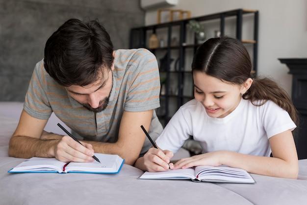 Escritura de padre y niña de alto ángulo