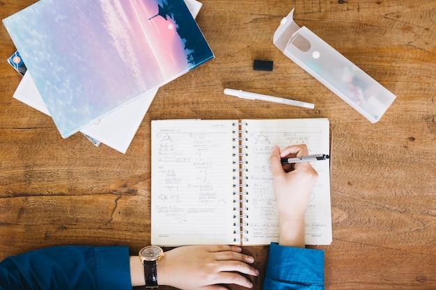 Escritura de la persona en el cuaderno