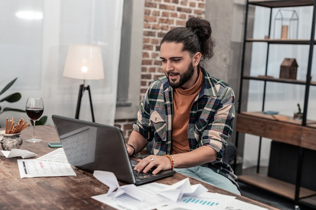 Escritura rápida. encantado de buen hombre escribiendo texto en la computadora mientras hace su trabajo