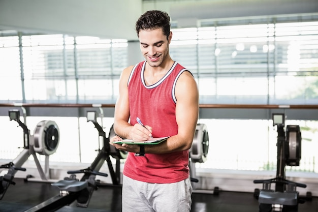 Escritura sonriente del hombre en el tablero en el gimnasio