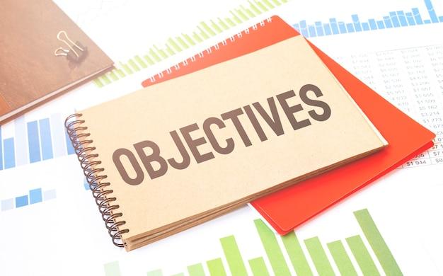 Escritura de texto word objetivos en el bloc de notas. concepto de negocio con bloc de notas rojo y cantidades financieras.