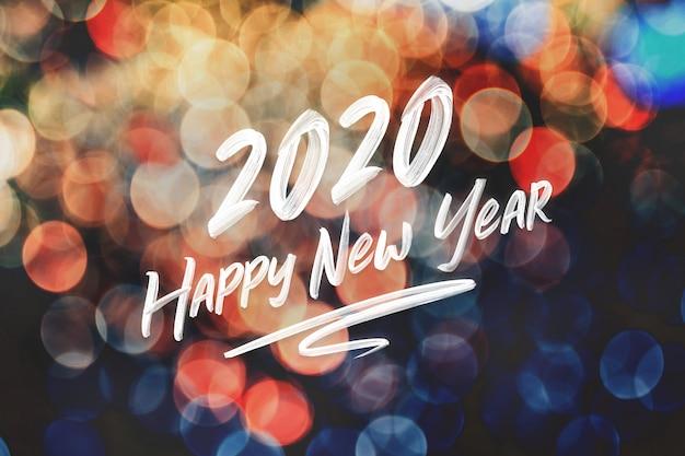 Escritura de trazo de pincel 2020 feliz año nuevo en abstracto festivo colorido bokeh luz de fondo