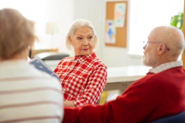Escucha atenta. inteligente mujer de edad seria mirando a su amigo mientras lo escucha atentamente