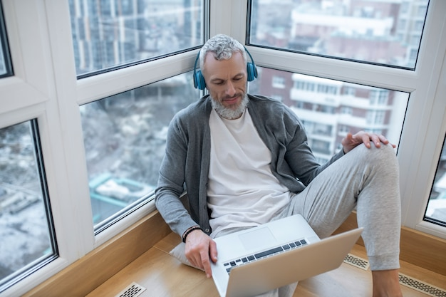 Escuchando algo. un hombre maduro con una computadora portátil y auriculares escuchando algo en internet