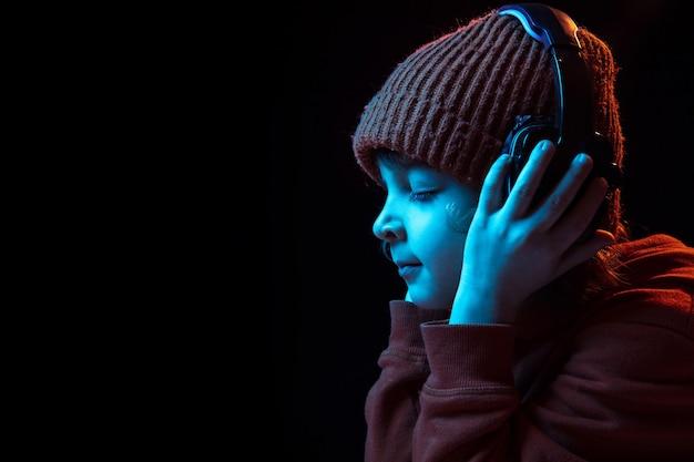 Escuchar música alegre en auriculares con los ojos cerrados. retrato de niño caucásico sobre fondo oscuro en luz de neón. concepto de emociones humanas, expresión facial, ventas, publicidad, tecnología moderna, gadgets.