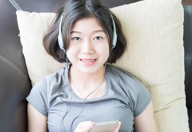 Escuchar música de mujer joven de teléfono móvil