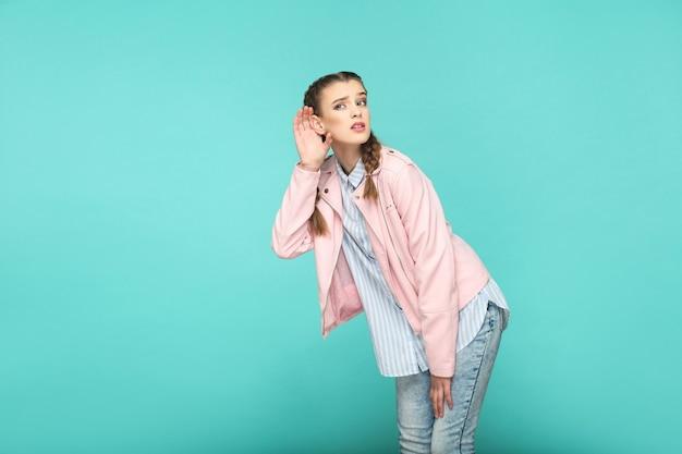 Escuchar el retrato entrometido de la hermosa linda chica de pie con maquillaje y peinado de coleta marrón en camisa azul claro a rayas chaqueta rosa. interior, tiro del estudio aislado en fondo azul o verde.