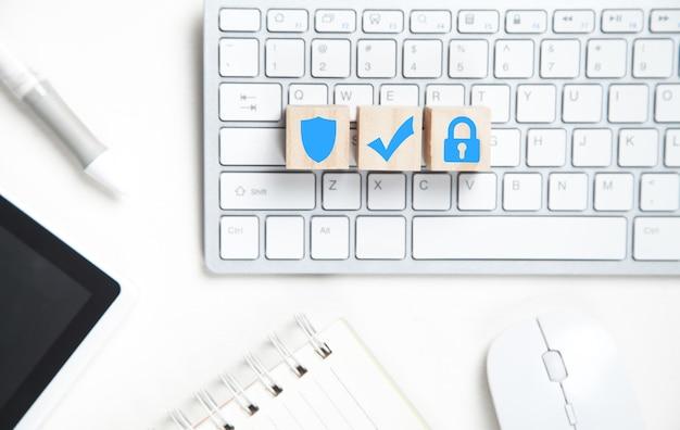 Escudo, marca de verificación, candado en cubos de madera. teclado y otros objetos comerciales. seguridad de internet y tecnología