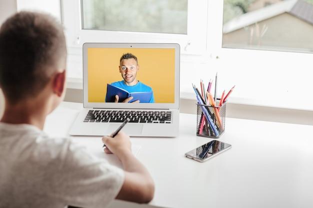 Escuela en casa a través de educación en el hogar en línea. el niño está sentado frente a la computadora
