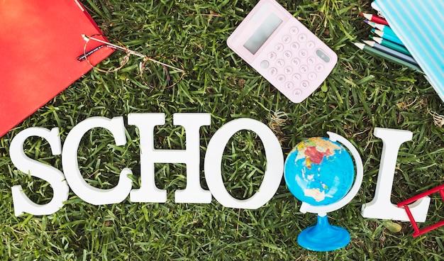 Escuela de palabras con globo y papelería sobre hierba.